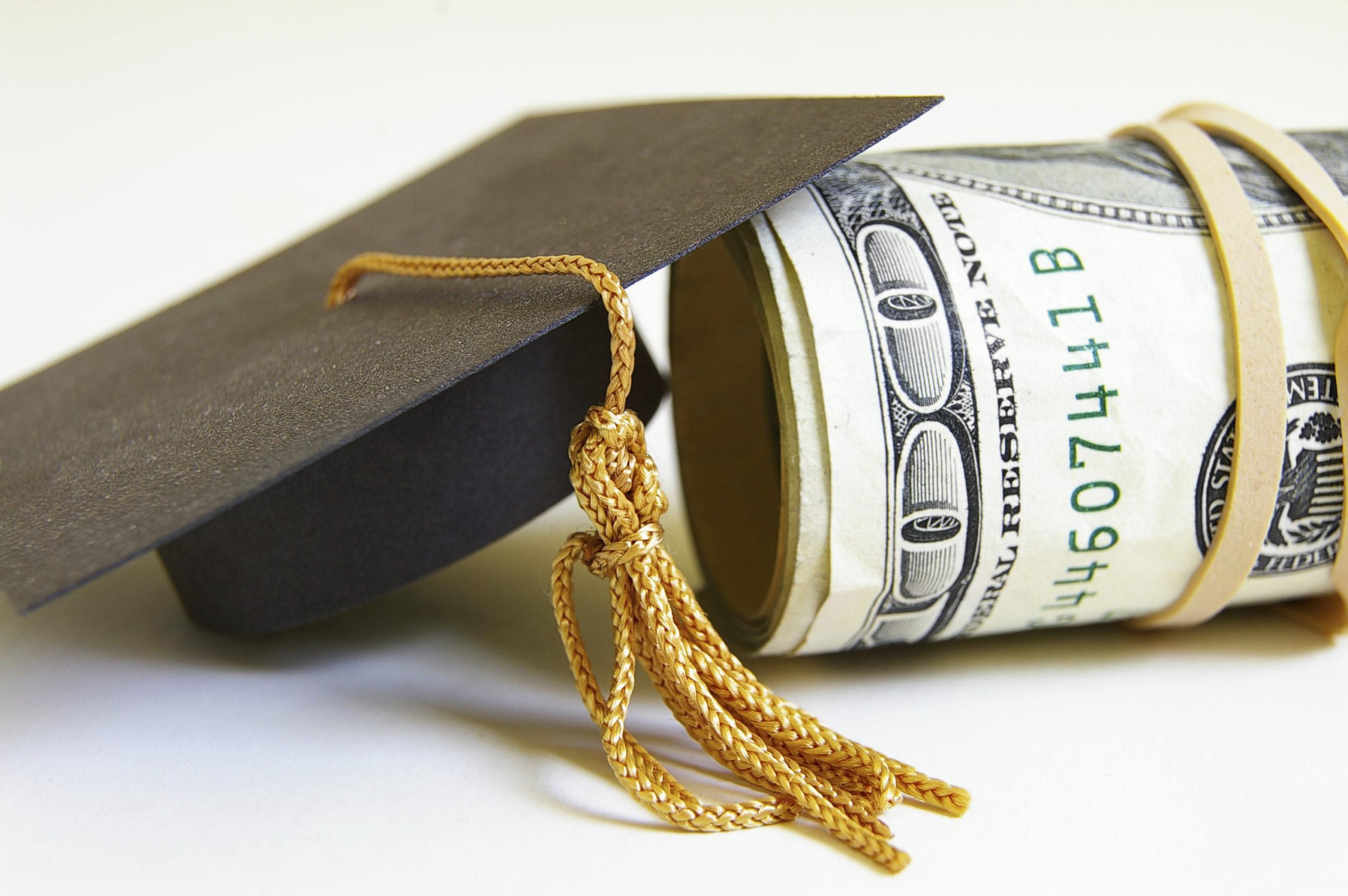 graduation cap and cash roll, closeup