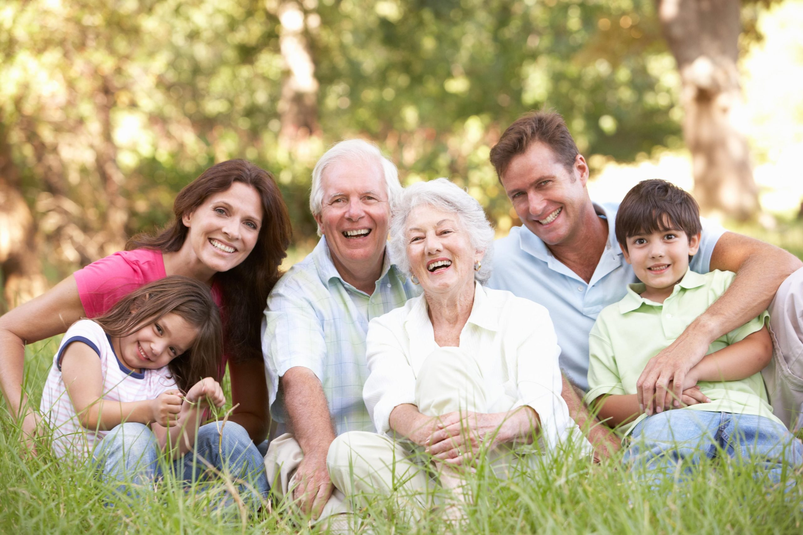 Three generation family sitting in the grass hugging together