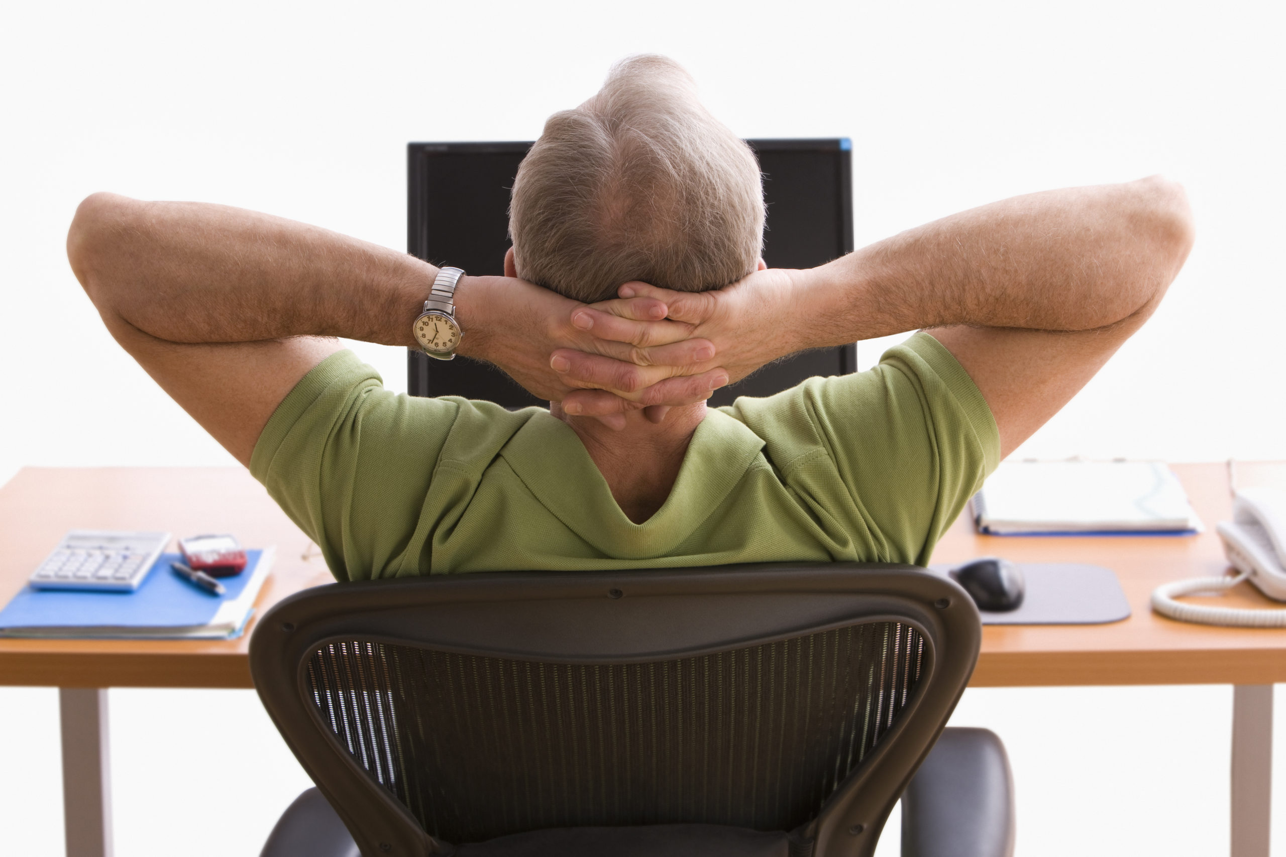 senior man leaning back in computer chair with hands behind his head looking at computer screen