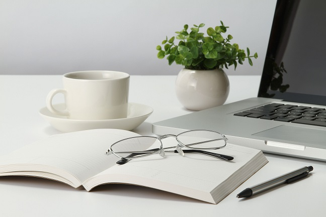 table with laptop, coffee, reading glasses, notebook and pen