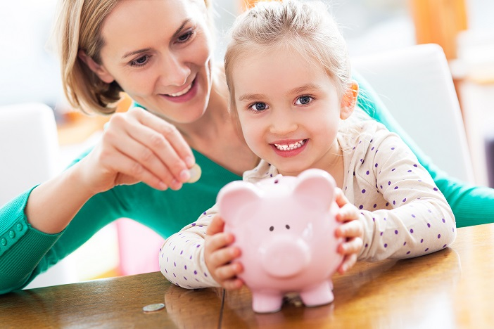 Mother teaching his daughter to save money in the piggy bank