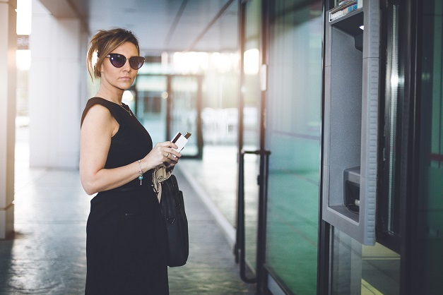 Young business woman holding credit card in front of the ATM