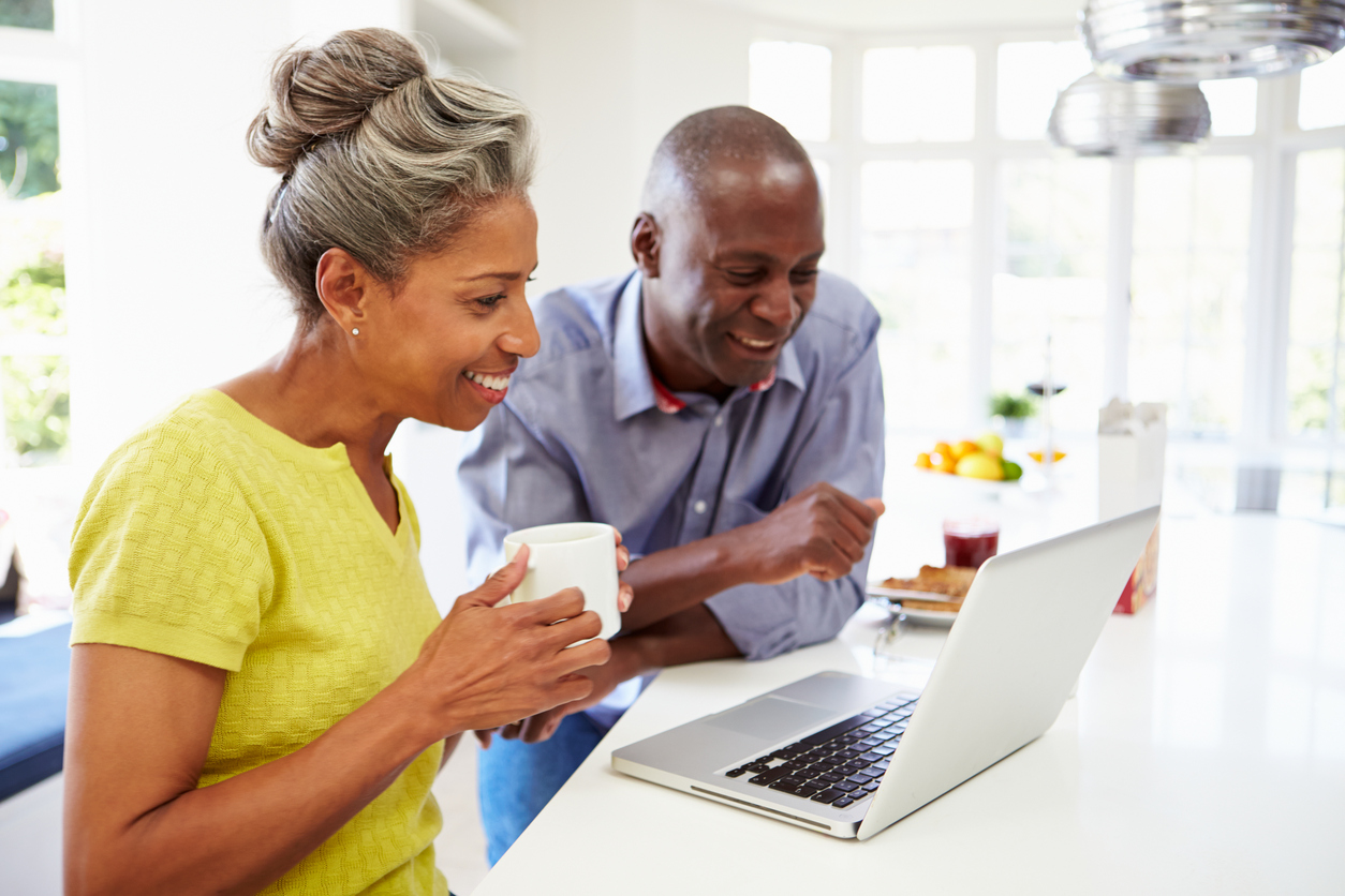 Mature African American couple using a laptop in a kitchen