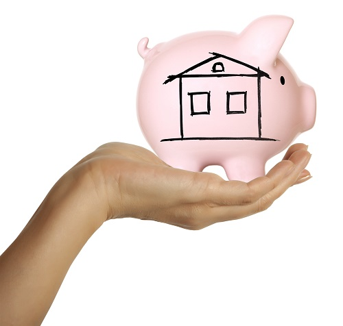 Hand holding a piggy bank with a house draw on it