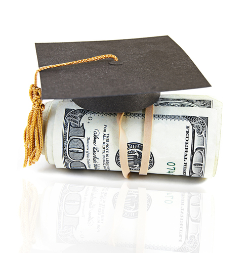 Mini graduation cap on rolled up cash
