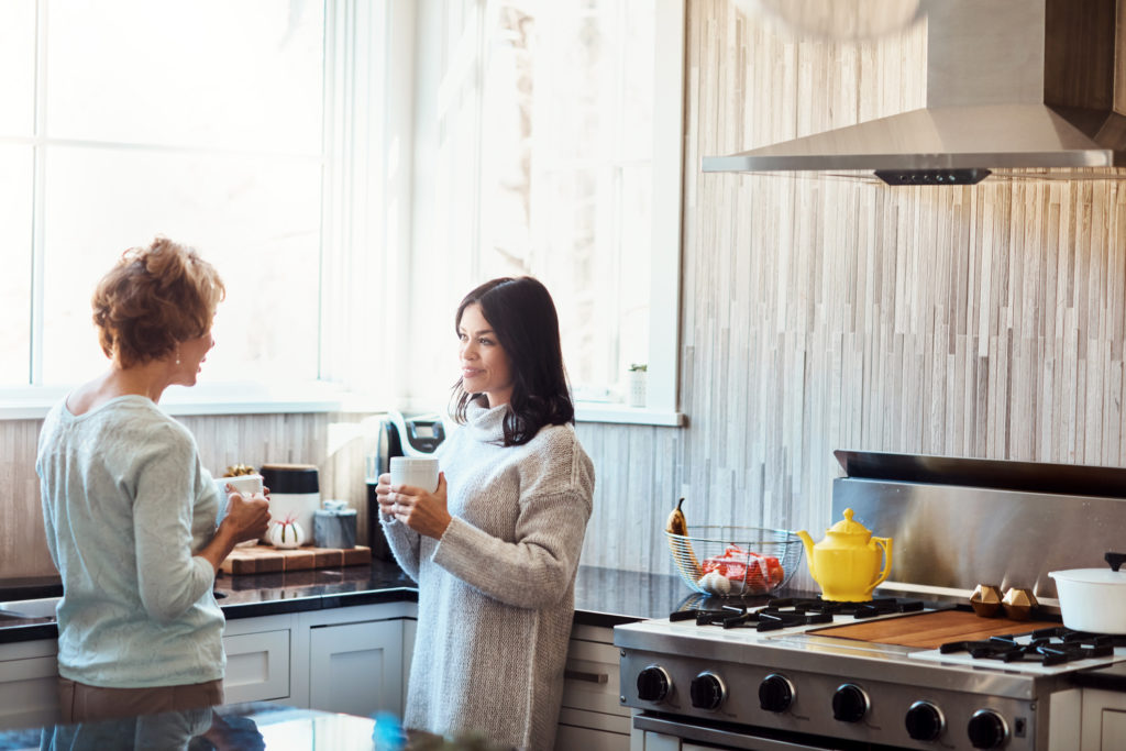 Shot of a young woman enjoying a coffee break and chat in the kitchen with her mother at home