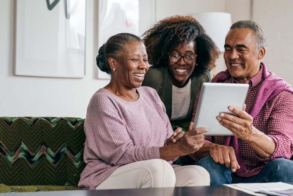 Senior couple looking at a tablet screen with their daughter