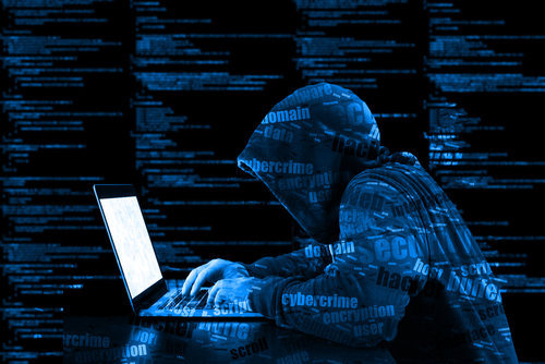 Hacker working in a computer covered with code