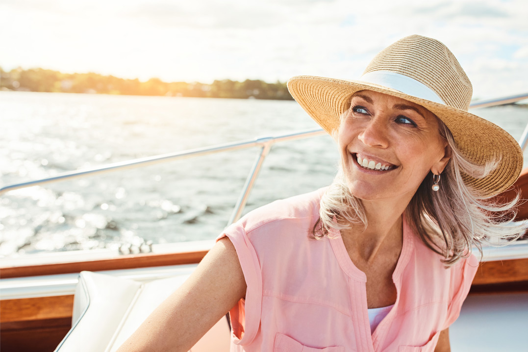 woman with hat smiling on a boat
