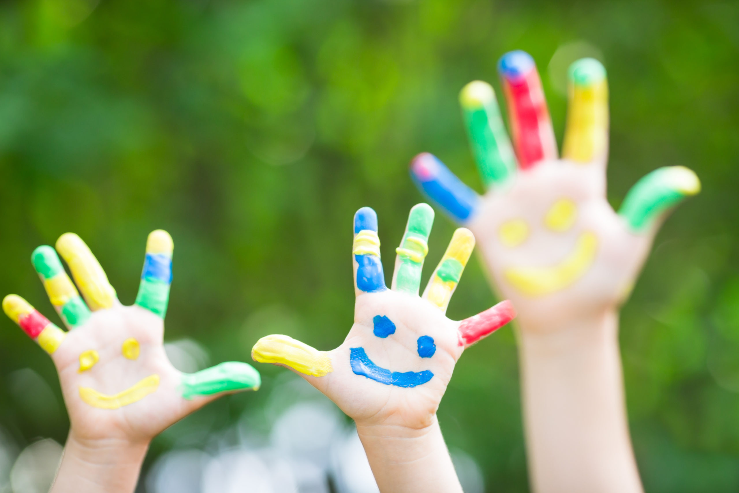 Kid hands with paint in their fingers and a happy face in the palm