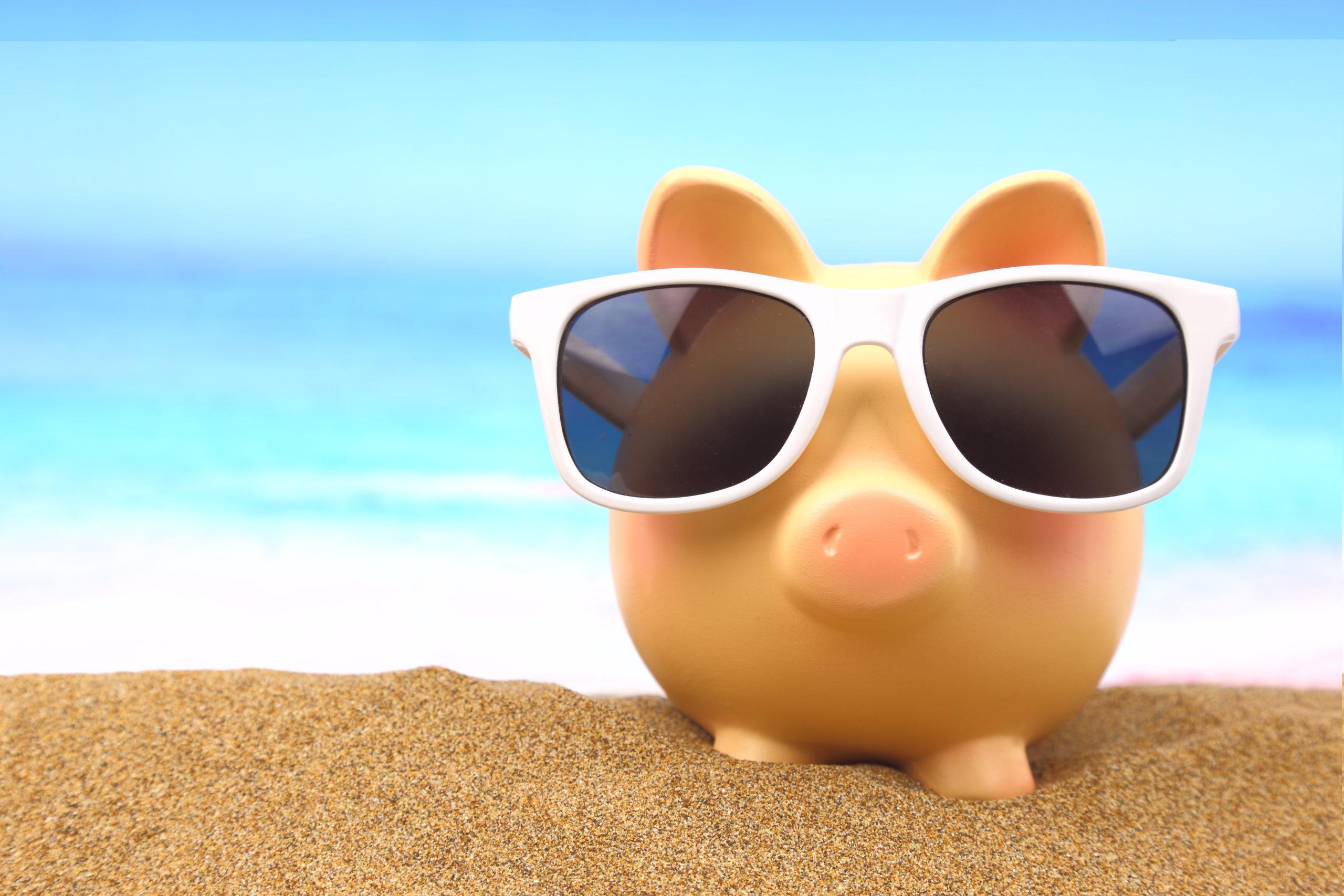 Piggy ba k in the beach wearing sun glasses