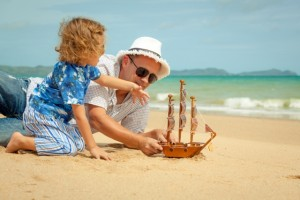 Father and son playing in the sand with a ship