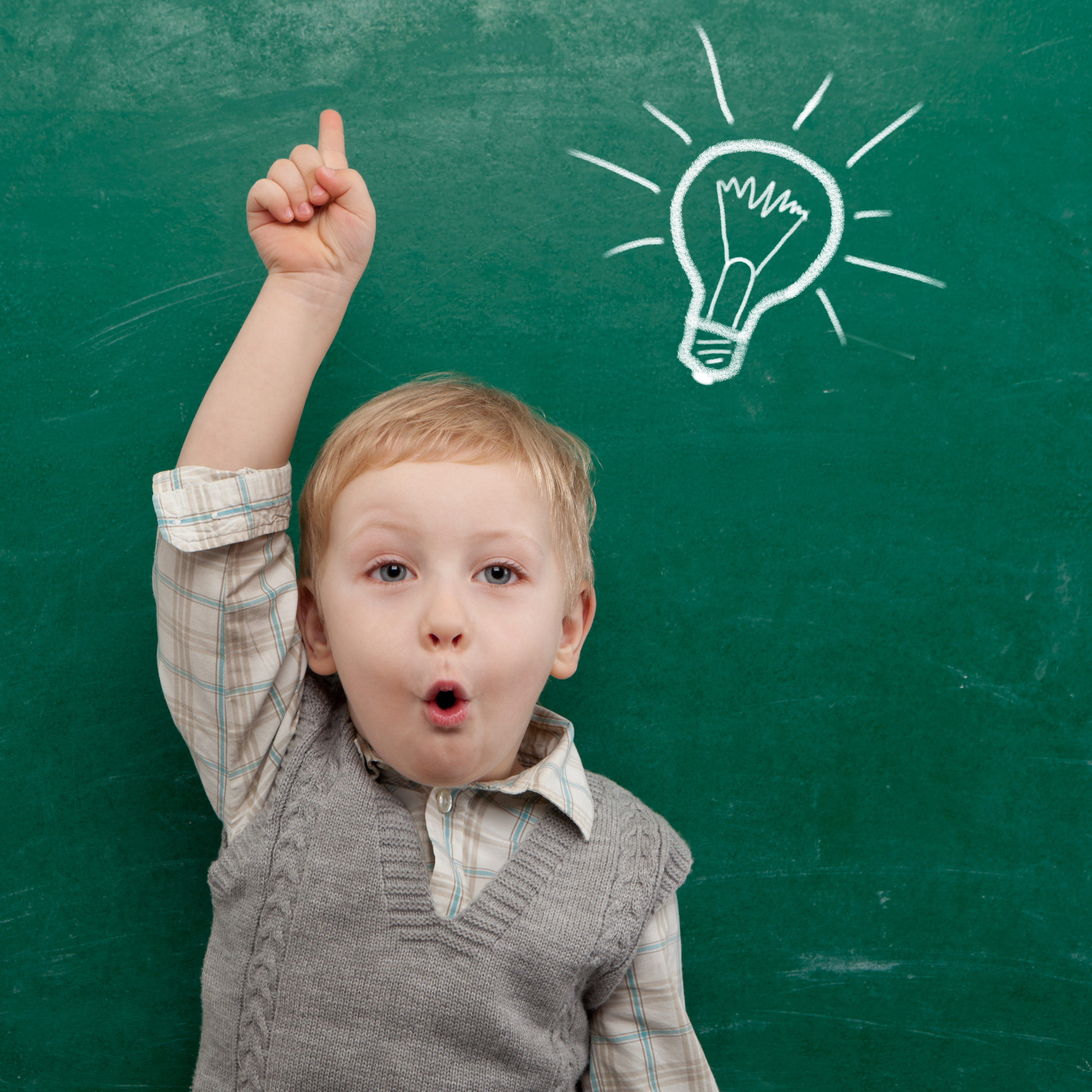 Kid raising his hand with surprise face and a bulb draw in a chalkboard