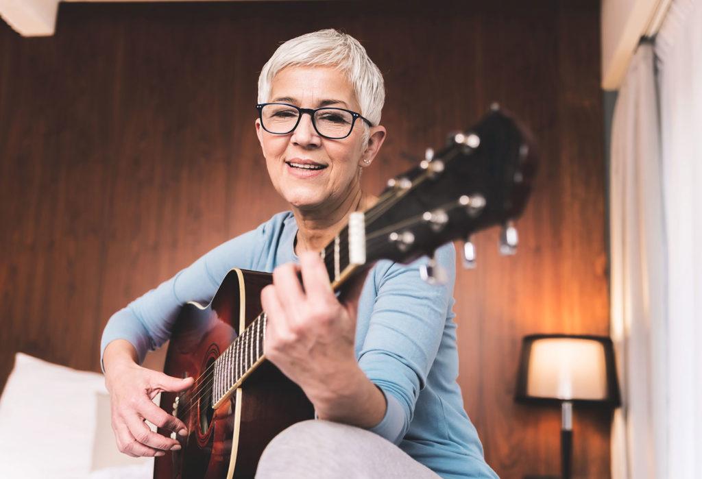 senior woman playing guitar