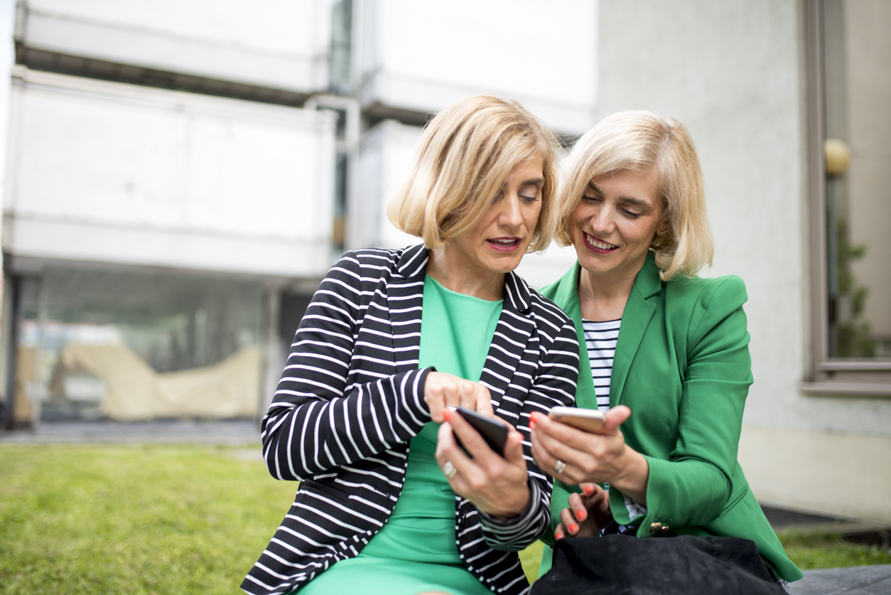 female twins comparing information on their cell phone screens