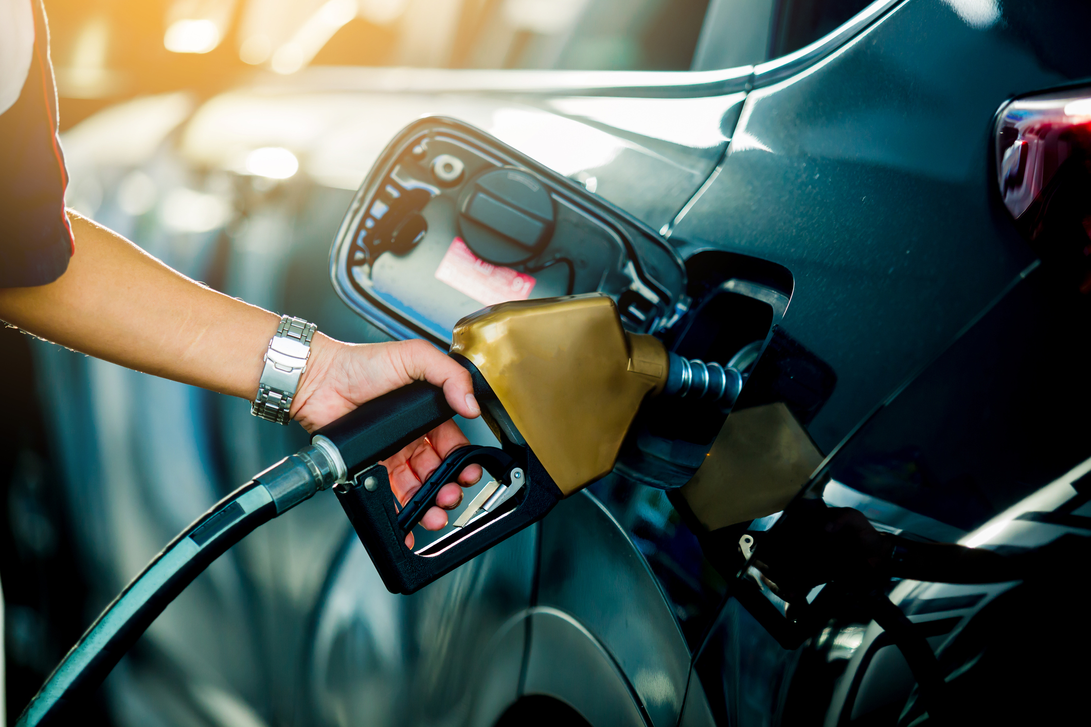 hand fueling gas into black car