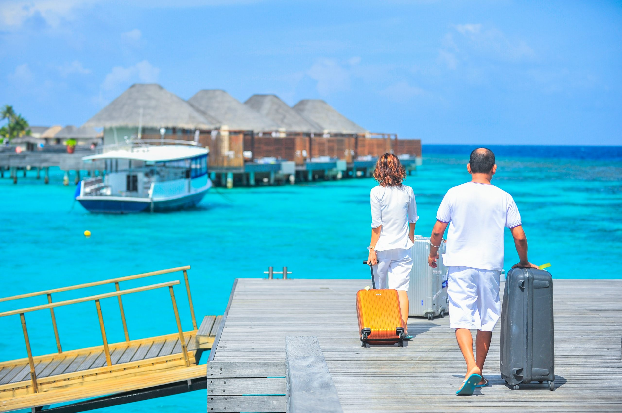 couple on a dock with suit cases walking to over water bungalows